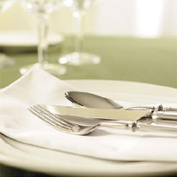 Besteck und Serviette auf einem Teller
